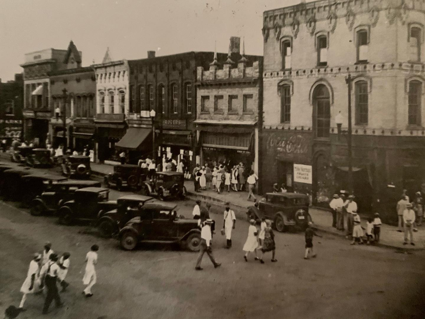 Newnan-Coweta County streets are busy with pedestrians and vintage cars in this black an white photo..