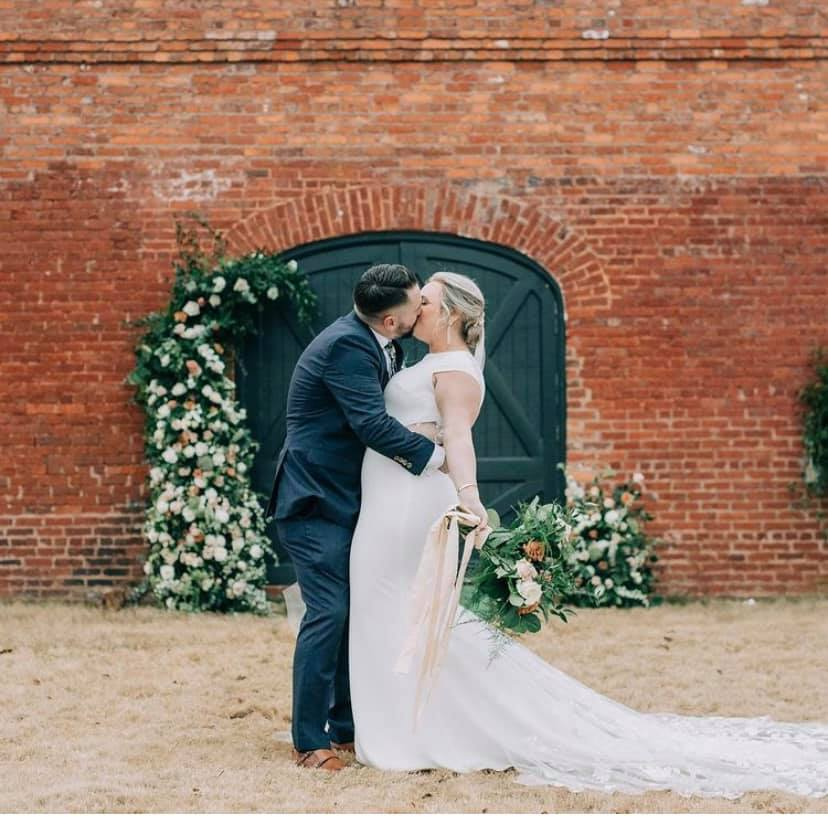 A bride and groom kiss in front of the Train Depot