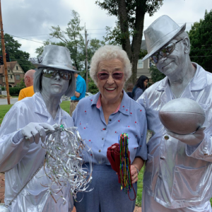 A member of the historical society poses with two silver-covered artists.